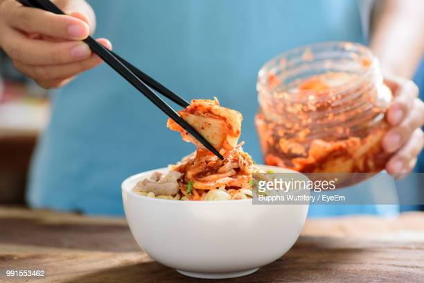midsection of woman using chopsticks while picking food from bowl on table - 韓国料理 ストックフォトと画像