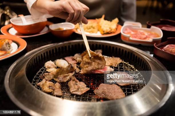 midsection of woman using chopsticks while picking food from metal grate - korean food stock pictures, royalty-free photos & images