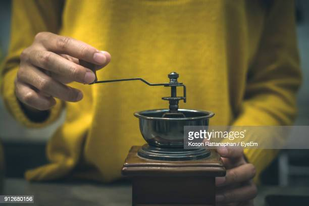 Midsection Of Woman Using Coffee Grinder