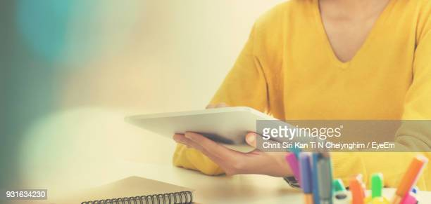 Midsection Of Woman Using Digital Tablet At Table