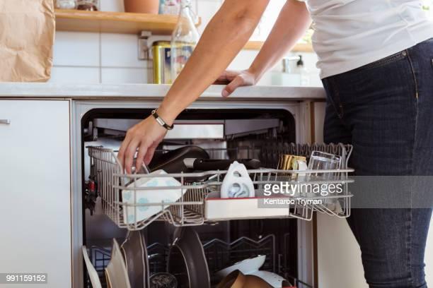 midsection of woman using dishwasher while standing in kitchen - bewogen beeldtechniek stockfoto's en -beelden