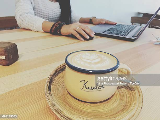 Midsection Of Woman Using Laptop By Coffee Served On Table At Cafe