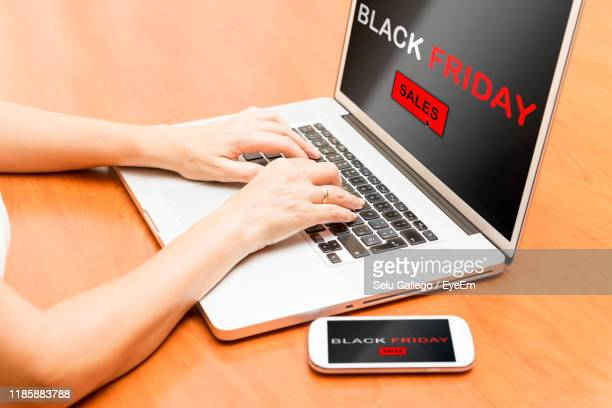 midsection of woman using laptop on table - black friday stock photos and pictures