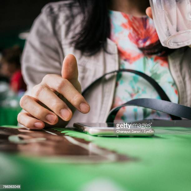 midsection of woman using mobile phone at table in cafe - chanayut stock photos and pictures