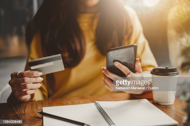midsection of woman using mobile phone on table at cafe - onlinebanking stock-fotos und bilder