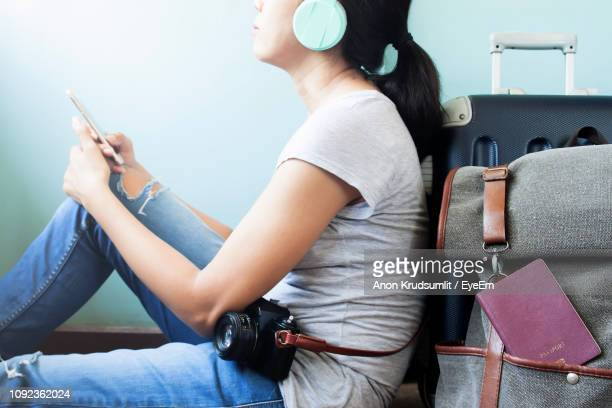 Midsection Of Woman Using Mobile Phone While Sitting With Luggage