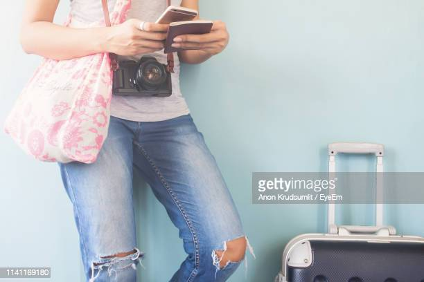 Midsection Of Woman Using Mobile Phone While Standing Against Wall