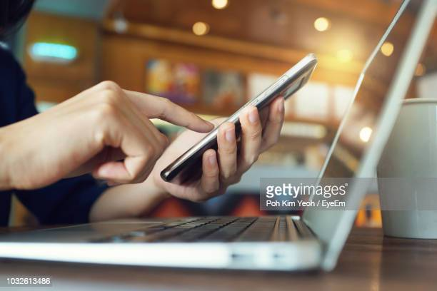 midsection of woman using mobile phone with laptop at desk - mid section stock pictures, royalty-free photos & images