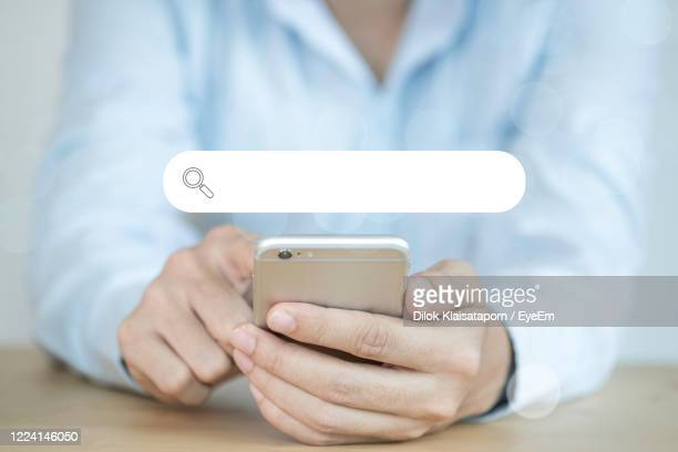 midsection of woman using mobile phone with search engine symbol - search engine stock pictures, royalty-free photos & images