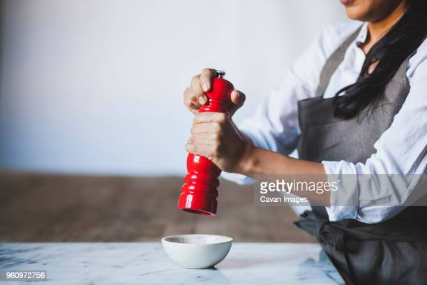 midsection of woman using pepper mill in kitchen - pepper mill stock pictures, royalty-free photos & images