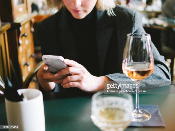 midsection of woman using phone in restaurant - auto post production filter stock pictures, royalty-free photos & images