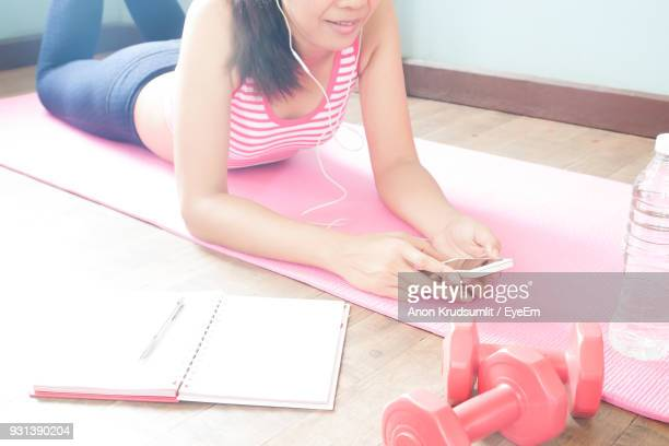 Midsection Of Woman Using Phone While Lying On Exercise Mat At Home