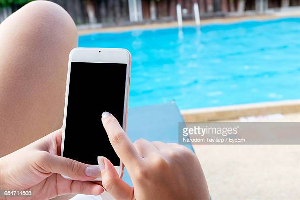 Midsection Of Woman Using Smart Phone At Poolside