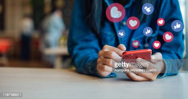 midsection of woman using smart phone on table in cafe - social media stockfoto's en -beelden
