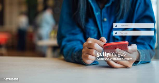 midsection of woman using smart phone on table in cafe - password stock pictures, royalty-free photos & images