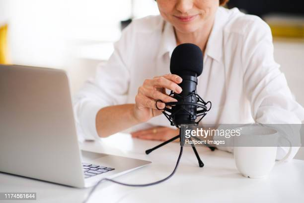 midsection of woman vlogger or blogger with laptop and microphone, talking. - podcast stock-fotos und bilder