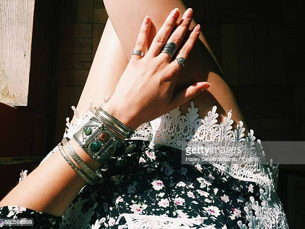 Midsection Of Woman Wearing Bangles And Rings During Sunny Day