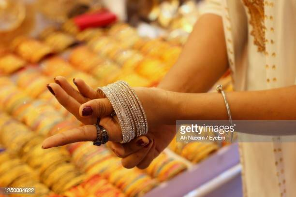 midsection of woman wearing bangles in shop - bangle stock pictures, royalty-free photos & images