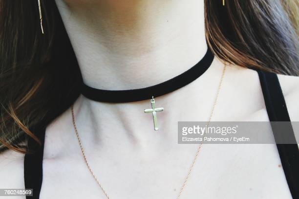 Midsection Of Woman Wearing Choker With Cross Pendant