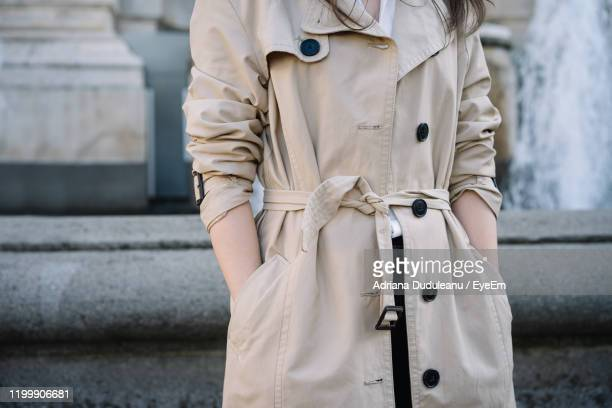 midsection of woman wearing coat - trench coat stock pictures, royalty-free photos & images