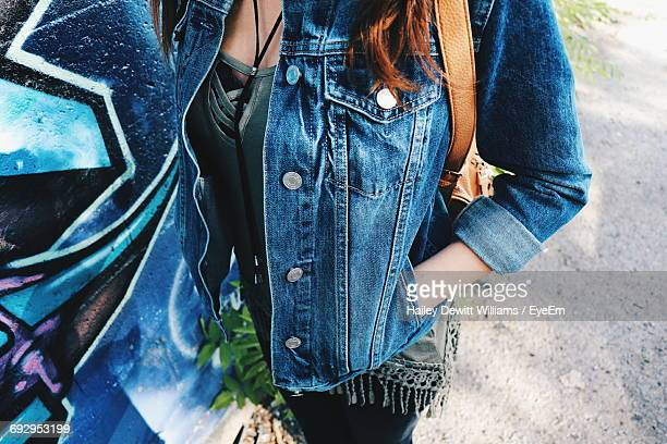 Midsection Of Woman Wearing Denim Jacket And Standing On Street