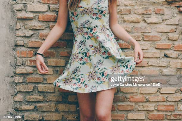 Midsection Of Woman Wearing Dress Standing Against Brick Wall