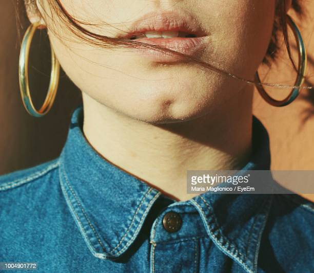 midsection of woman wearing earrings - earring stock pictures, royalty-free photos & images
