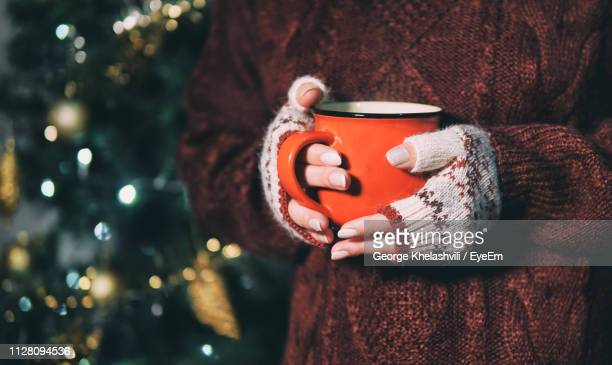midsection of woman wearing fingerless gloves holding coffee mug against christmas tree during winter - 指なし手袋 ストックフォトと画像