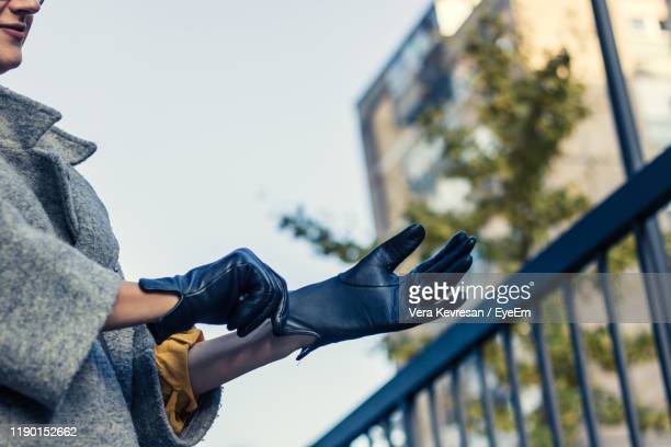 midsection of woman wearing gloves against sky - leather glove stock pictures, royalty-free photos & images