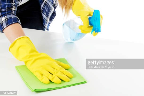midsection of woman wearing gloves cleaning table against white background - ゴム手袋 ストックフォトと画像