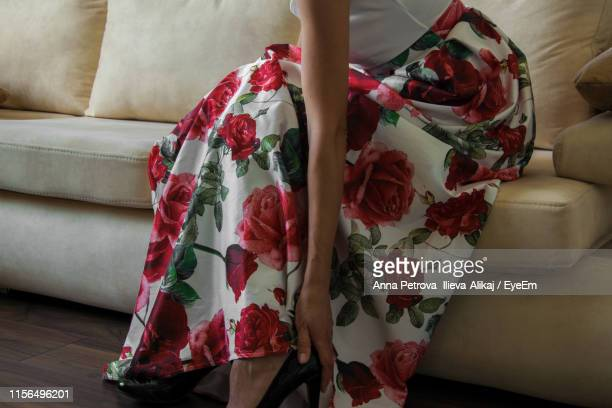 midsection of woman wearing high heels at home - robe à motif floral photos et images de collection