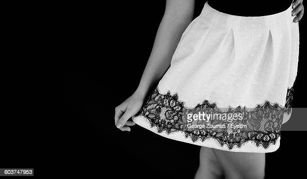 Midsection Of Woman Wearing Mini Skirt Against Black Background