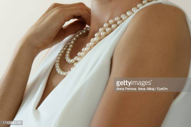 midsection of woman wearing necklace against white background - pearl necklace stock pictures, royalty-free photos & images