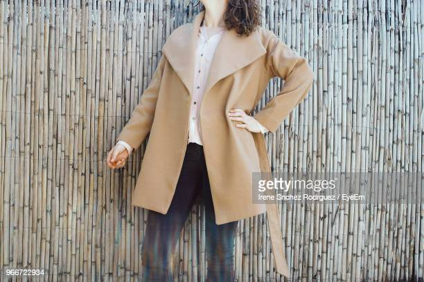 midsection of woman wearing overcoat by bamboo wall - overcoat stock pictures, royalty-free photos & images