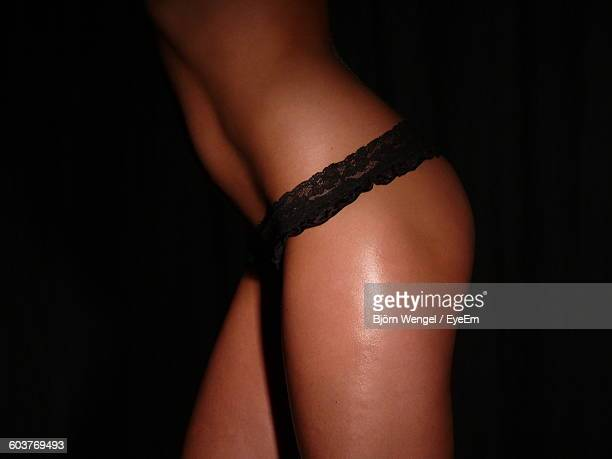 Midsection Of Woman Wearing Panties In Darkroom