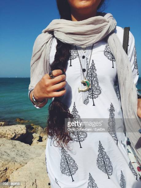 midsection of woman wearing salwar kameez standing on rocks by sea against sky - salwar kameez stock pictures, royalty-free photos & images