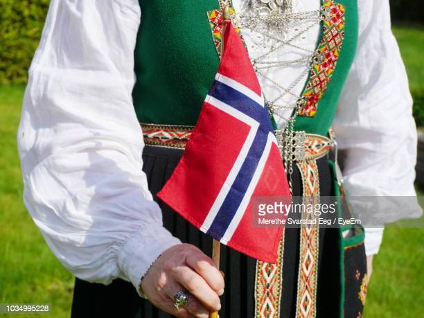 midsection of woman wearing traditional clothing while holding norwegian flag - norwegian flag stock pictures, royalty-free photos & images