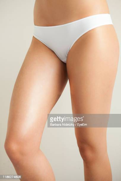 midsection of woman wearing underwear while standing against white background - femmes en culottes photos et images de collection