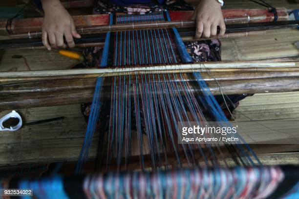 Midsection Of Woman Weaving Textile