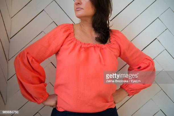 Midsection Of Woman With Arms Akimbo Standing At Home