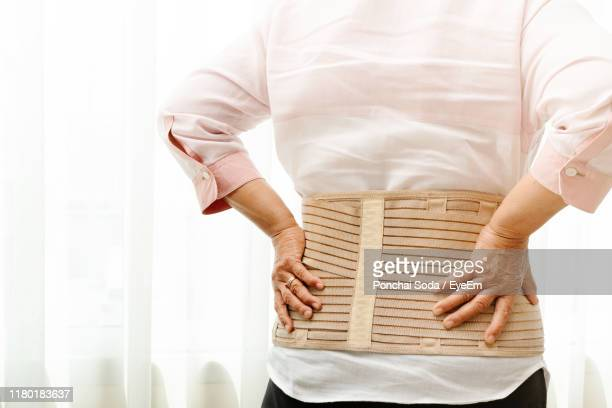 midsection of woman with backache at home - belt stock pictures, royalty-free photos & images