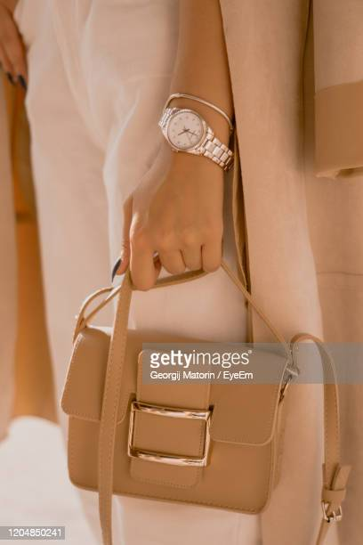 midsection of woman with bag - brown purse stock pictures, royalty-free photos & images