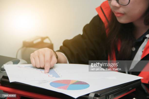 Midsection Of Woman With Bar Graph And Pie Chart On Table At Office