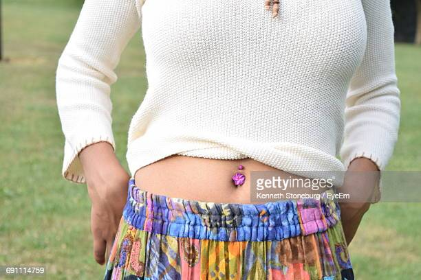 midsection of woman with belly ring in park - belly ring stock photos and pictures