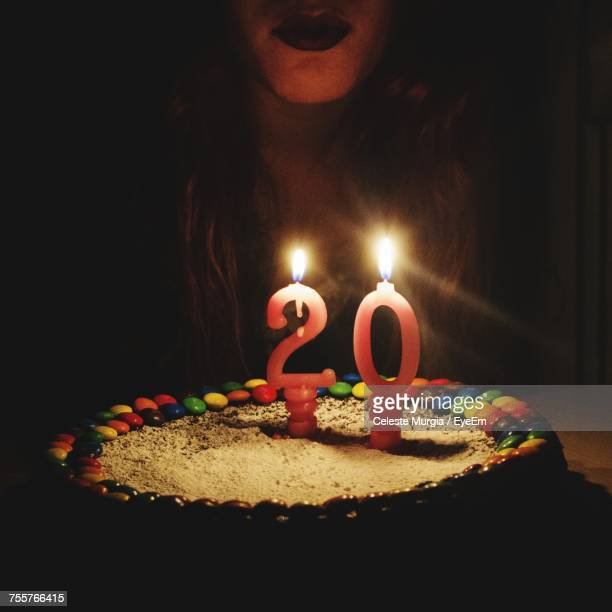midsection of woman with birthday cake on table in darkroom - number 20 stock pictures, royalty-free photos & images