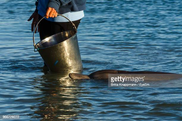 Midsection Of Woman With Bucket Standing In Sea