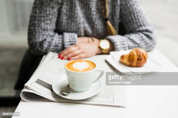 Midsection of woman with coffee and newspaper sitting at shop