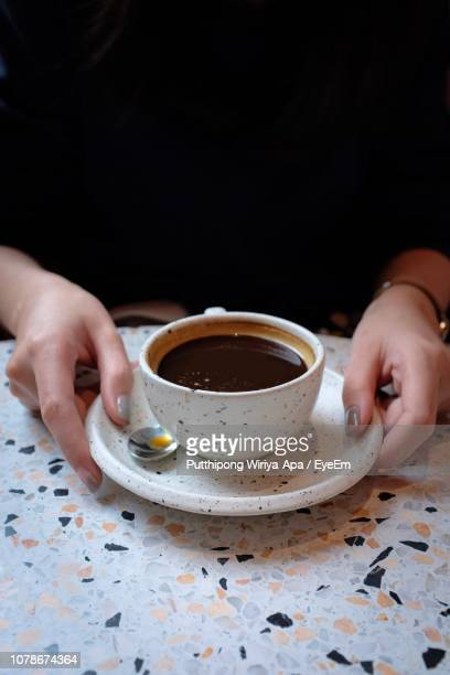 Midsection Of Woman With Coffee In Cup On Table