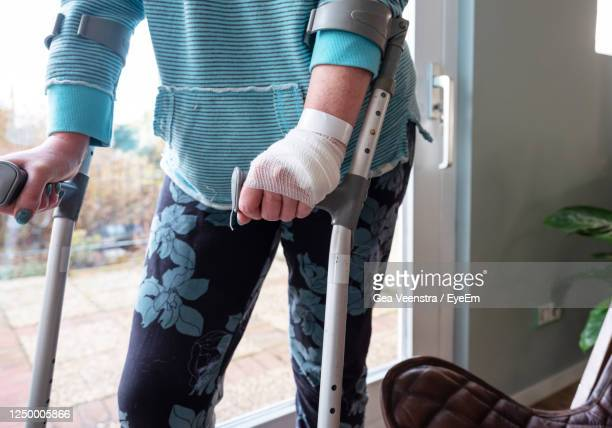 midsection of woman with crutch walking in home - 包帯 ストックフォトと画像