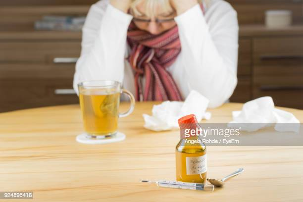 midsection of woman with drink and medicine bottle on table - angela rohde stock-fotos und bilder